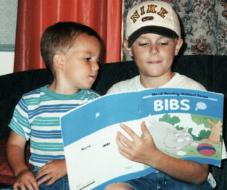 Kenny, age 8, teaching Jason, age 3, to read.